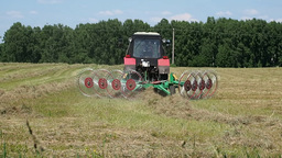 Farm Work In The Field Tractor Collects Mown H stock footage