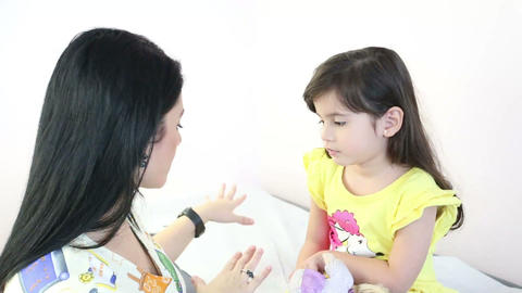 Beautiful therapist preparing a little girl to giv Stock Video Footage