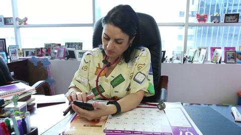 Female Doctor Reading Message At Mobile Phone stock footage
