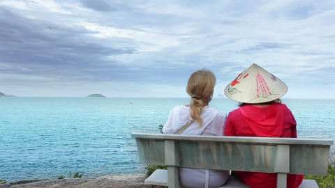 Two women sitting on a bench talking at the sea Footage