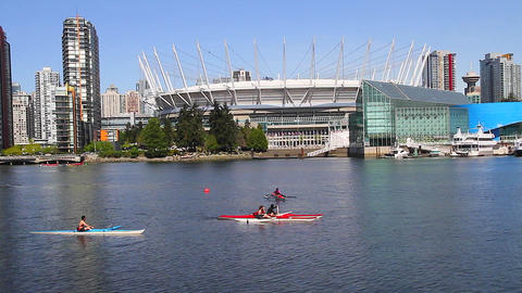 people paddling in front of new bc place Stock Video Footage