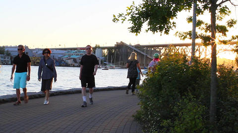 sunset - people walking on yaletown seawall Footage