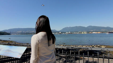 girl watches float plane from Stanley park Stock Video Footage