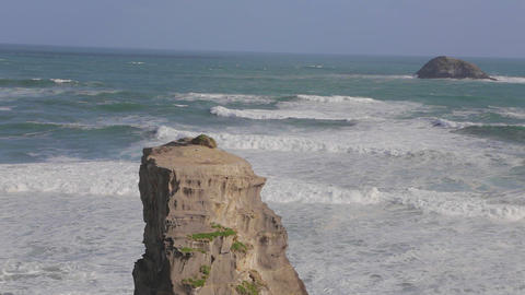 wide still shot of murawai ocean rock formation an Footage