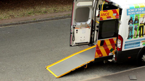 Ambulance with open doors and extended ramp park o Footage
