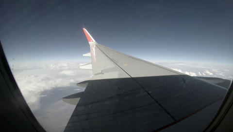 2.7K. Airplane wing out of window on blue sky back Footage