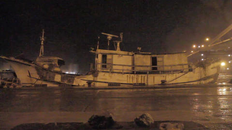 Ghostly boat at harbor during a typhoon with stron Stock Video Footage