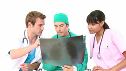 Multiethnic medical team examining an x-ray Stock Video Footage