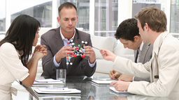 Confident manager holding a molecule in a meeting Footage