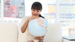 Young businesswoman looking at a terrestrial globe Stock Video Footage