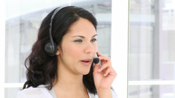 Brunette business woman talking on headset Footage