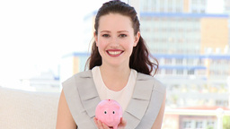 Smiling business woman inserting coin in a piggyba Stock Video Footage
