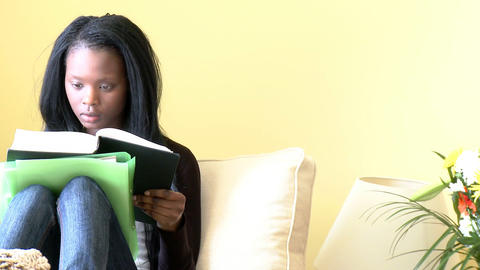 Ethnic woman reading a book sitting on sofa Footage