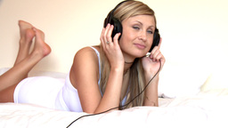 Blond woman listening music lying on bed Footage