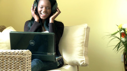 Afroamerican woman using a laptop with headset on Footage