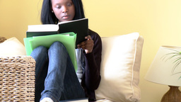 Interested woman reading a book sitting on sofa Footage