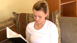 Quiet woman reading a book sitting on sofa Footage