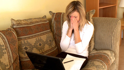 Pessimistic woman sitting on sofa using a laptop Stock Video Footage
