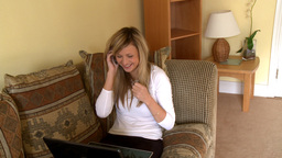 Merry woman on phone using a laptop Footage