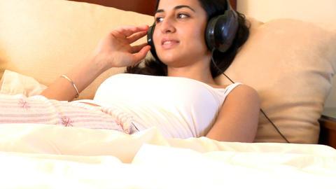 Elegant woman listening music with headphones lyin Stock Video Footage