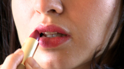 Close up of a brunette woman putting lipstick Stock Video Footage
