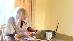 Concentrated woman doing her accounts using a lapt Footage