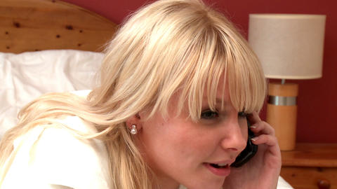 Portrait of a pretty woman talking on phone lying Stock Video Footage
