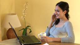 Serious woman on phone working at a computer Footage