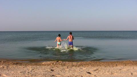 running swimming couple on beach Stock Video Footage