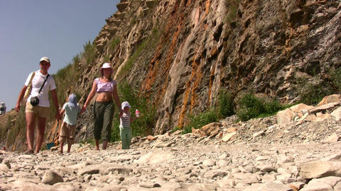 walking family on stone beach Stock Video Footage