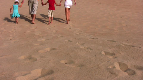 behind family of four on sand Stock Video Footage