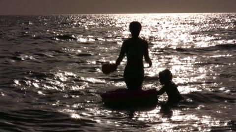 silhouette mother with children in water Footage