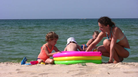 mother with children play on beach Stock Video Footage