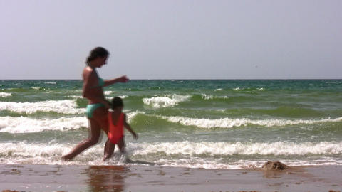 walking mother and little girl on beach Stock Video Footage