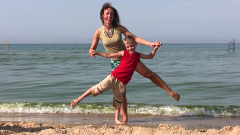 mother and son stand on one leg on beach Stock Video Footage