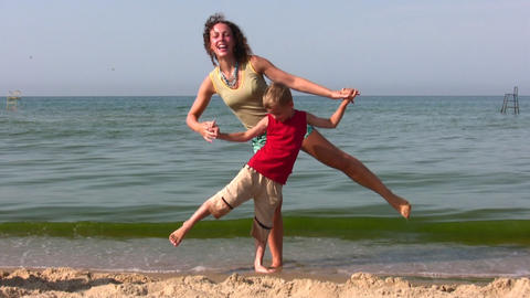 mother and son stand on one leg on beach Footage