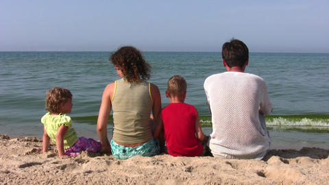 behind family of four sitting on beach Footage