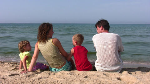 behind family of four sitting on beach Stock Video Footage