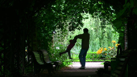 father rotate girl silhouette in plant tunnel Footage