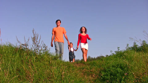 family with little girl walking on meadow Stock Video Footage