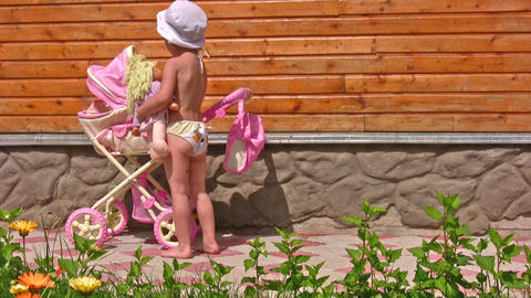 little girl with toy baby carriage Stock Video Footage
