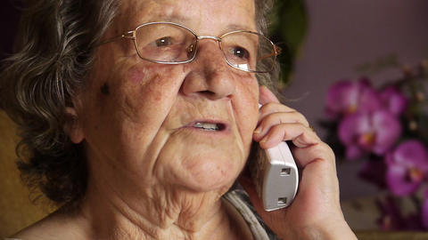 Old retired woman talking on phone Stock Video Footage