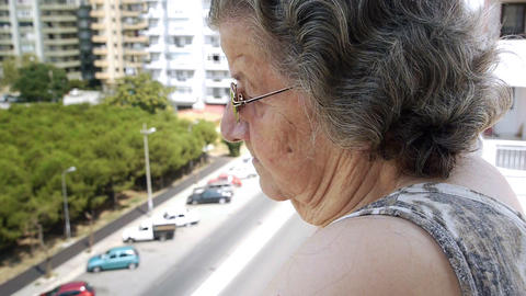 Old retired woman watching traffic Stock Video Footage