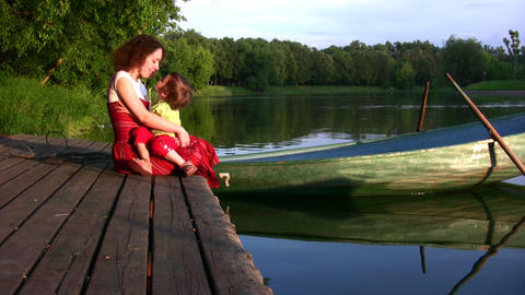Mother with girl on pond and boat Stock Video Footage
