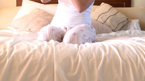 Young woman putting blush sitting on bed Stock Video Footage