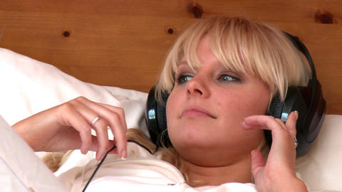 Portrait of a blond woman listening music lying on Stock Video Footage