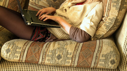 Attractive woman using a laptop sitting on sofa Stock Video Footage