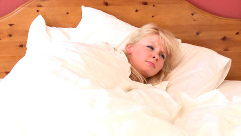 Blond woman waking up slowly Footage