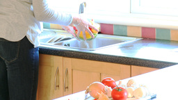 Young woman rinsing vegetables to make a salad Footage