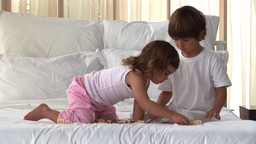 Wellbehaved children playing on the bed Footage